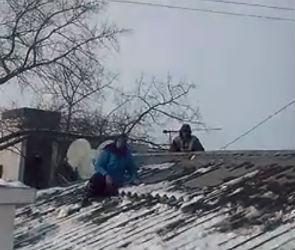 На видео попала старушка, сражающаяся на крыше с коммунальщиками